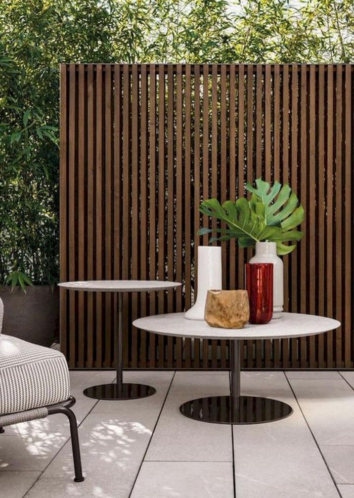 Minimalistische und schlichte Außeneinrichtung, zwei runde Tische, Vase mit grünen Blättern, Zaunideen Sichtschutz Inspiration