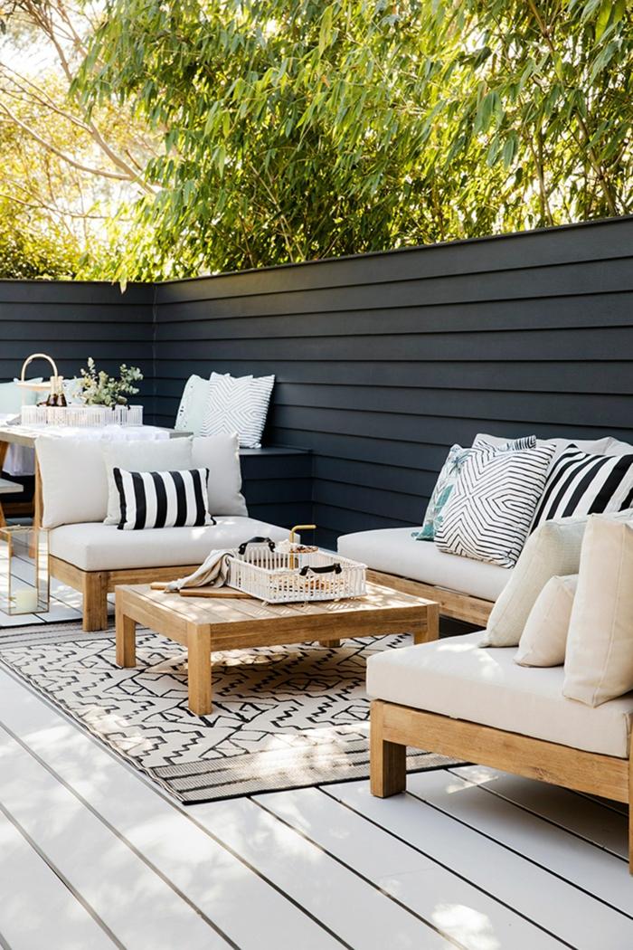 Terrassen Ideen Bilder mit Sichtschutz, dunkelblauer Gartenzaun, elegante Gartenmöbel mit weißer Polsterung, schwarz weiße Kissen