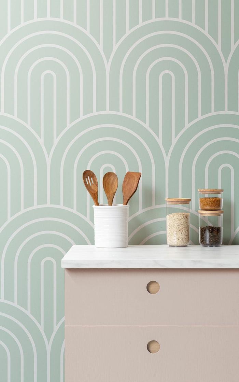 eleganter pinker Schrank, grüne Küchen Tapten mit Wellenlinien, Becher mit Löffeln aus Holz,