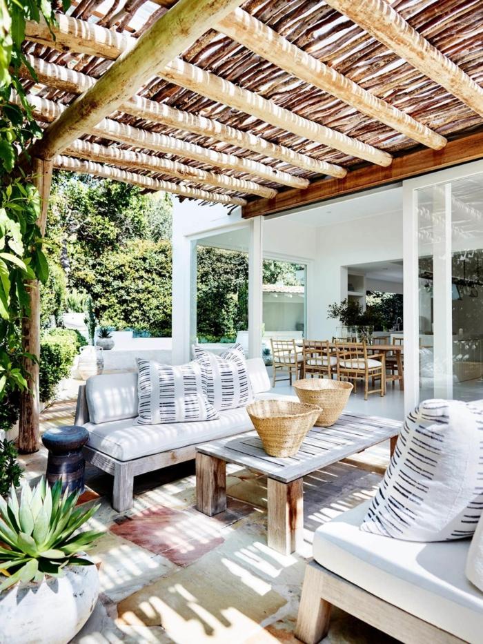Schutzdach aus runden Holzbalken und Bambus, weiße Gartenmöbel, Sichtschutz Pflanzen Garten