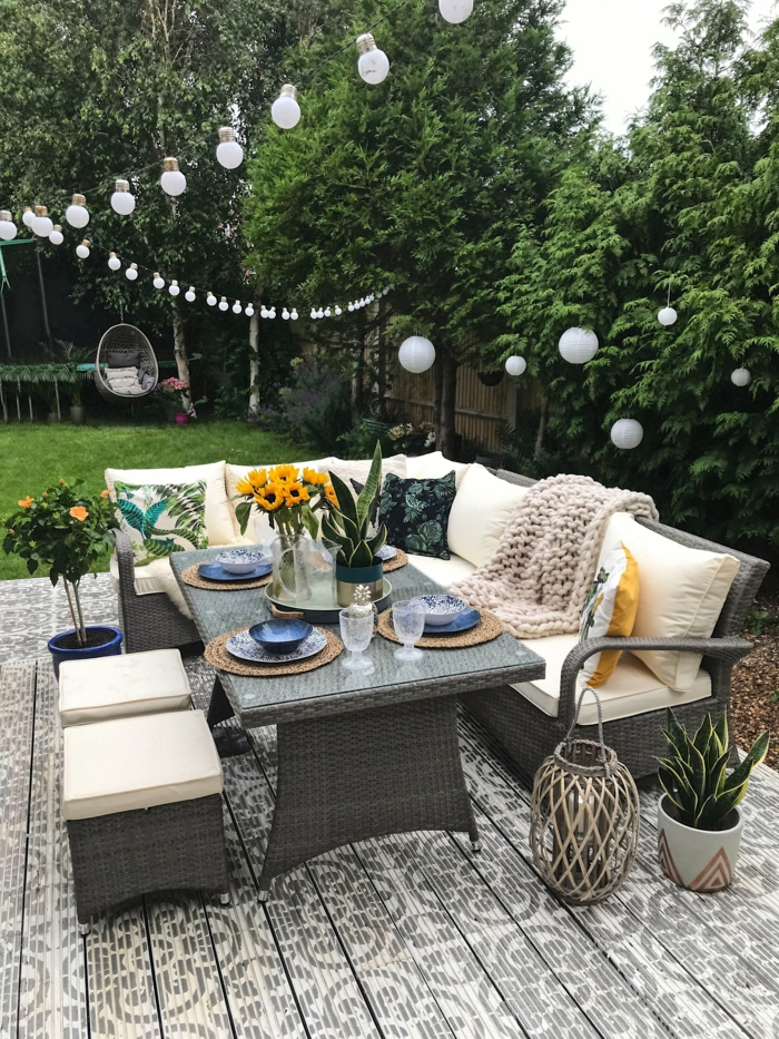 Pflanzen als Sichtschutz zum Nachbarn mit Gartenzaun, aufgehängte kleine Leuchten, Ecksofa und großer gedeckter Tisch