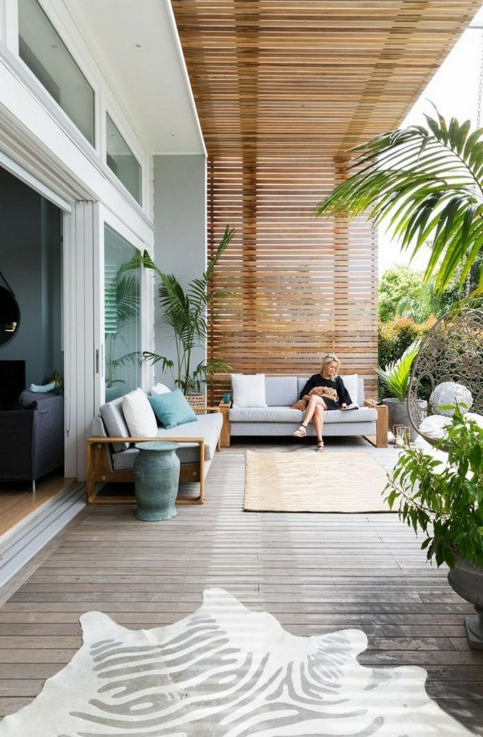 Terrassengestaltung mit Sichtschutz, luxuriöse Außeneinrichtung mit Gartenzaun aus Holz, junge Frau sitzt auf einem Sofa,