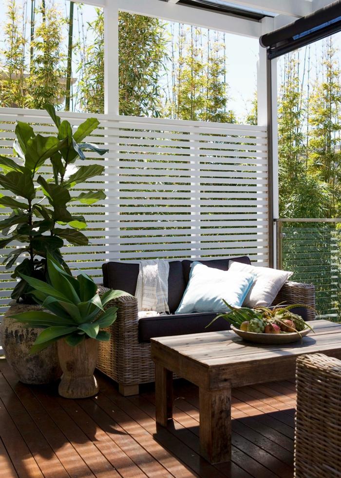 Terrassengestaltung mit Sichtschutz, weiße Lattenrost auf Fenster, Möbel mit schwarzer Polsterung, grüne Pflanzen