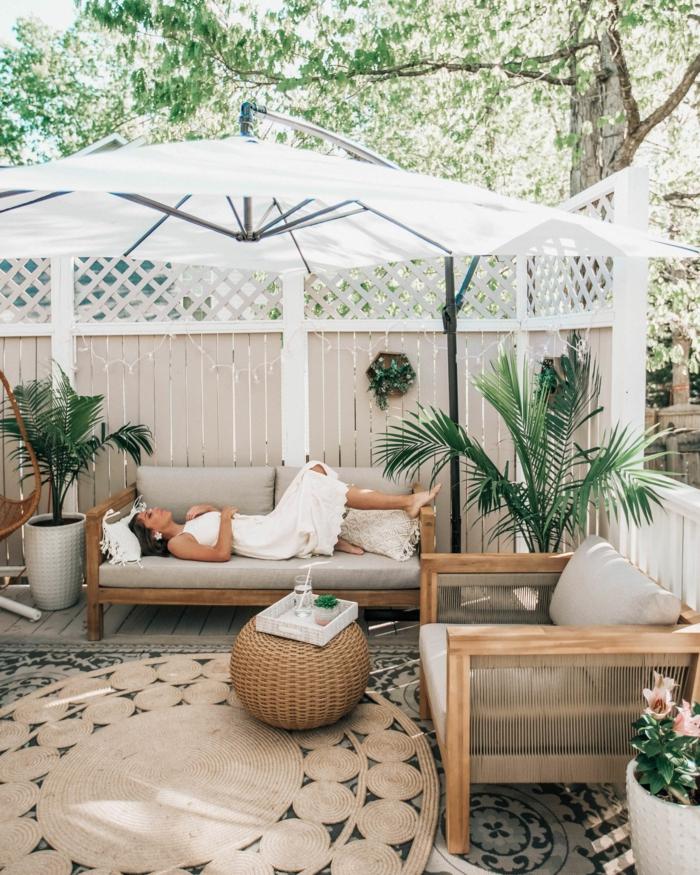 Garten Trennwand Holz in weiß, großer weißer Sonnenschirm, junge Frau liegt auf einem Sofa, Dekoration mit Pflanzen