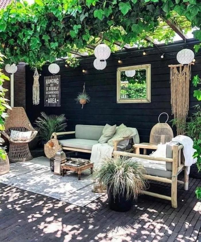 Sichtschutz Holz modern, schwarzer Gartenzaun, Schutzdach mit Pflanzen, Außeneinrichtung mit modernen Möbeln, bohemischer Stil