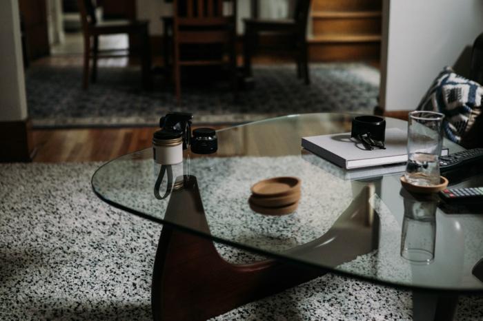 Teppich für Wohnzimmer in grau mit schwarzen Pünktchen, großer Glastisch, Inneneinrichtung Ideen