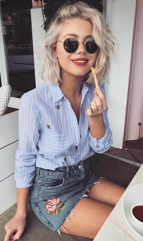 blonde Dame mit runden Sonnenbrillen, Kurzhaarfrisuren 2020 Bob, Sommer Outfir, blaues Hemd mit weißen Streife und Jeans Rock