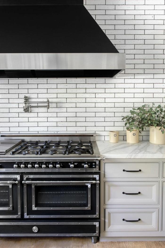 Abwaschbare Tapete Küche mit Flieseneffekt, weiße Schränke und schwarzer Offen, Dekoration mit Pflanze