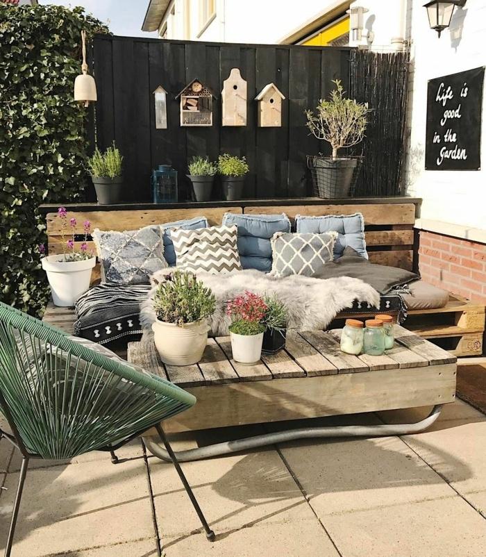 schwarzer Gartenzaun Ideen Bilder, drei aufgehängte Vogelhäuser, Upcycling Ideen, Sofa und Tisch aus alten Kisten, blaue Kissen