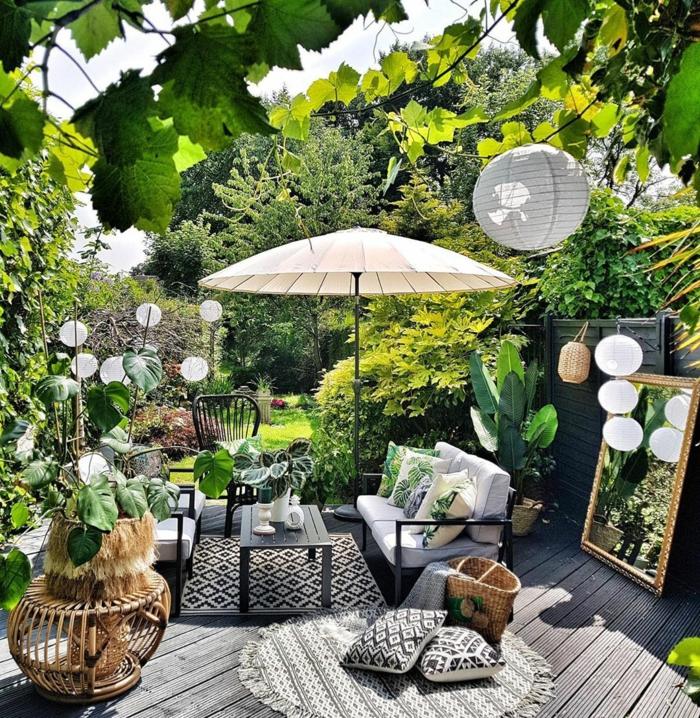 Sichtschutz Pflanzen Garten, moderne Gartenmöbel in schwarz, großer beiger Sonnenschirm
