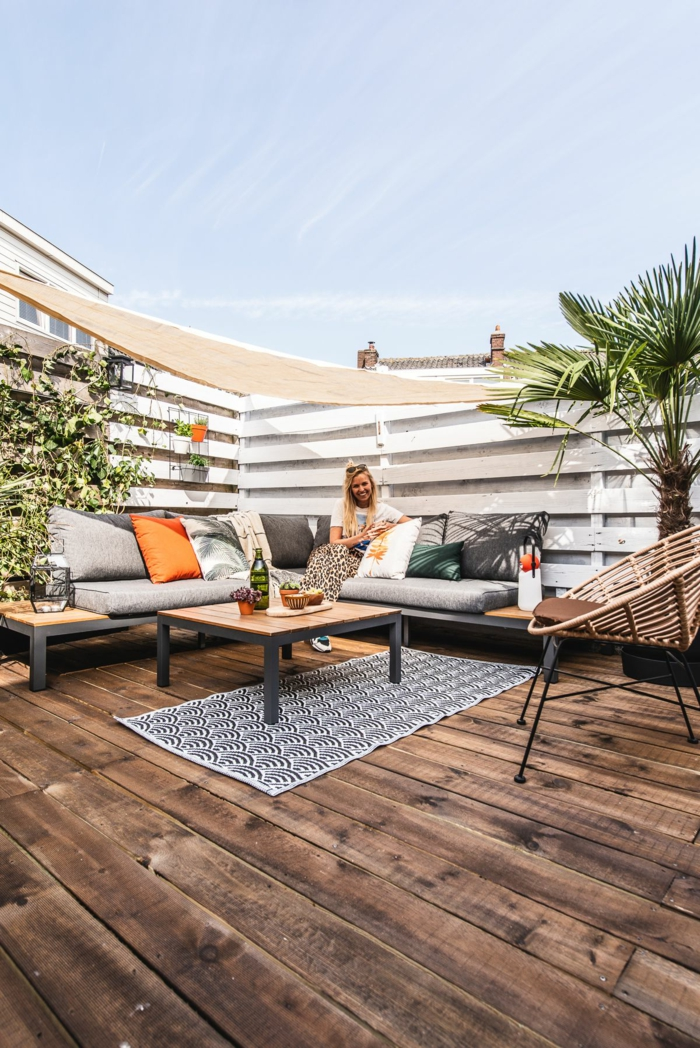 Gartenzaun Sichtschutz Holz modern, junge blonde Frau sitzt auf einem modernen Ecksofa, Pflanzen und Palme als Dekoration