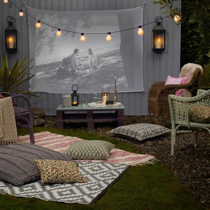 Weiße Wand mit Leinwand im Hinterhof, aufgelegte Decken und Kissen auf den Boden, Gartenzaun Ideen Gestaltung