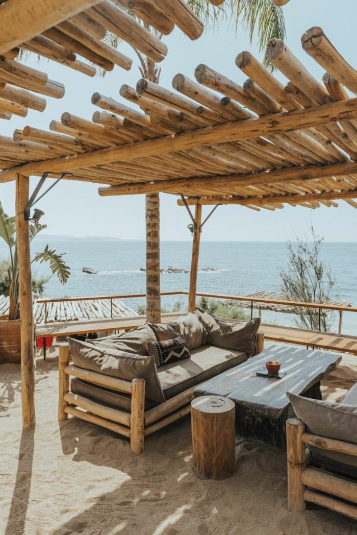 Terrasse mit Aussicht zum Meer mit Schutzdach aus Rundholz, zwei bequeme Sofas mit vielen Kissen