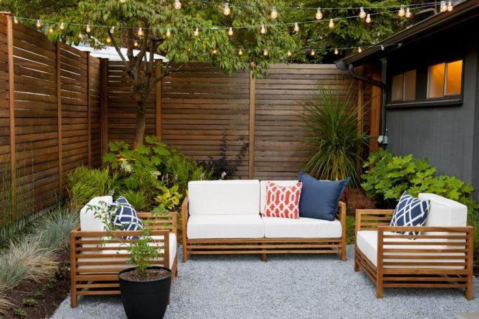 Garten Trenndwand Holz, aufgehängte kleine Leuchten, Holzmöbel mit weißer Polsterung und bunten Kissen
