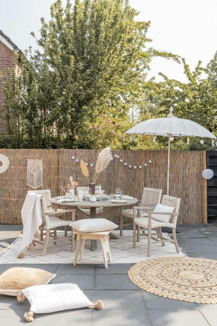 elegante Einrichtung von einem Garten mit Sichtschutz. Zaunideen aus Bambus, runder Tisch mit Stühle und Sonnenschirm