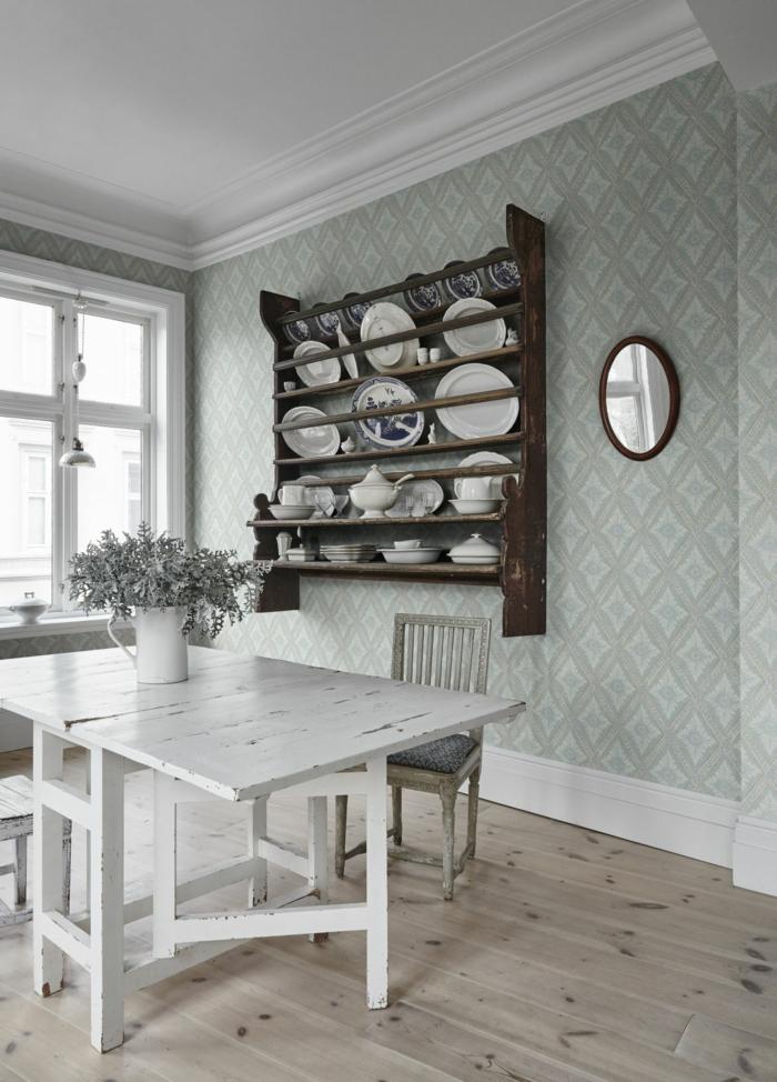 Inneneinrichtung im skandinavischen Stil, weißer Tisch aus Holz, altmodisches Regal mit Tellern