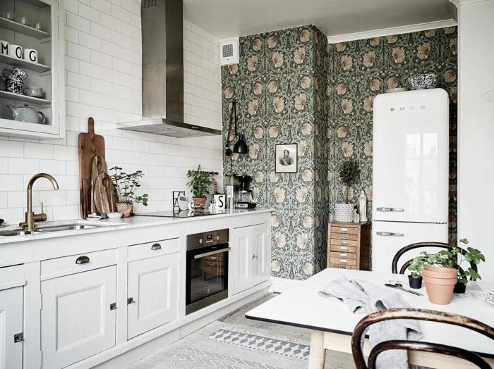Inneneinrichtung im skandinavischen Stil, weiße Schränke und Fliesen, grüne abwaschbare Tapete Küche mit Blumen
