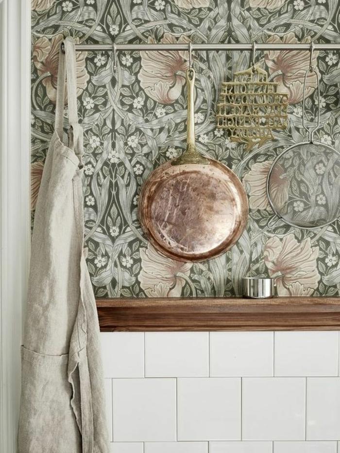 Wandgestaltung Küche Beispiele, aufgehängte Pfanne aus Kupfer, blassgrüne Tapete mit Blumen