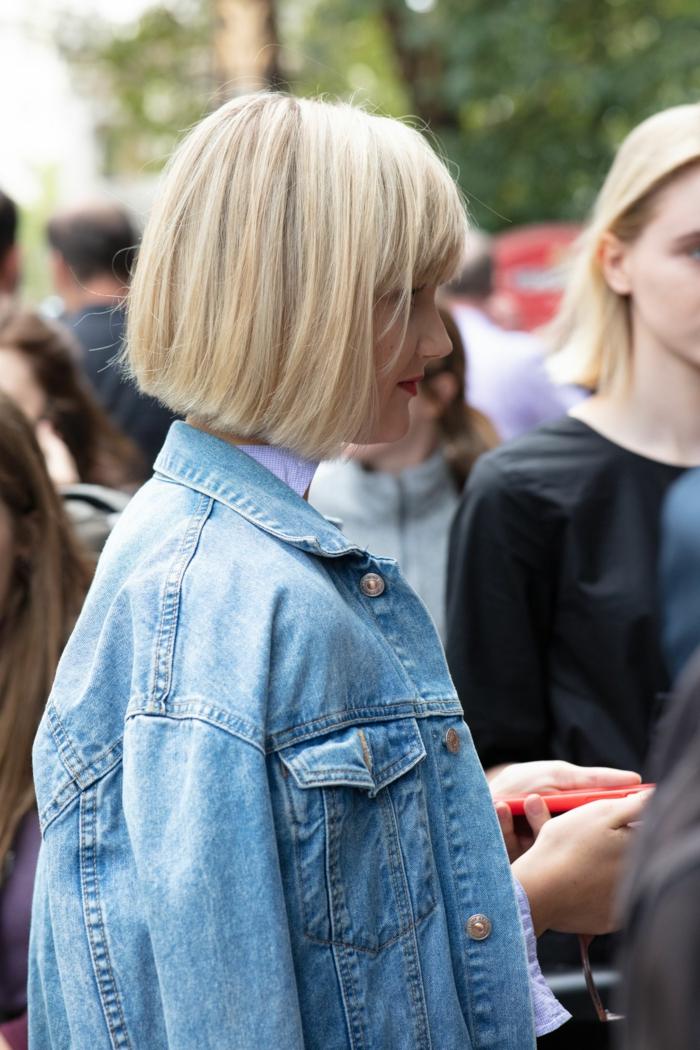 Frisuren Frauen Mittellange, sportlich elegant angezogene Dame, blaue Jeansjacke, Frisuren 2020 Frauen Mittellang, blonde Haare und Bob Schnitt