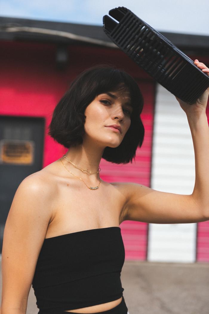 Frau hält Tasche über den Kopf, schwarzes Top, dunkle Haare, Kurzhaarfrisuren Frauen 2020,