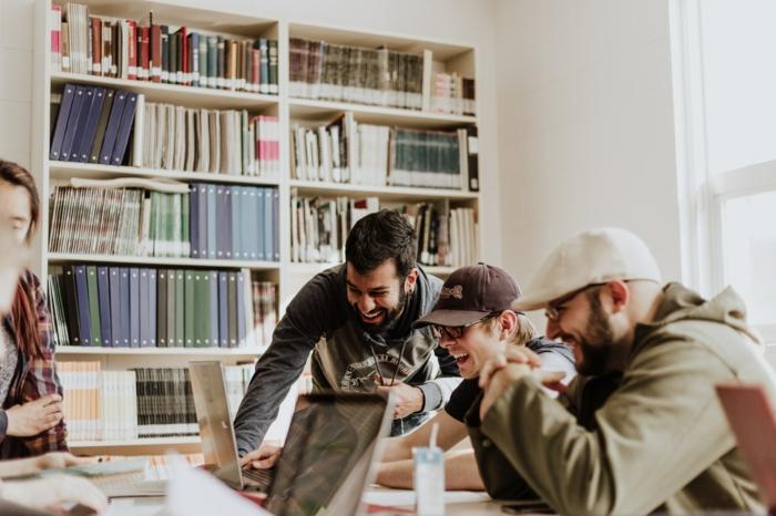 Studenten lernen zusammen, Studieren mit Erfolge, Regal mit vielen Büchern, berufliche Weiterbildung Deutschland, drei junge Männer