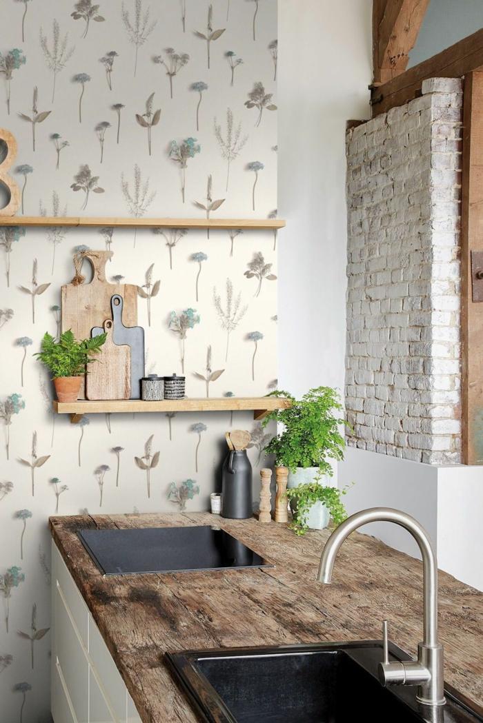 weiße Backsteinwand, weiße Schränke mit Theke aus Holz, Tapeten für die Küche mit Blumen