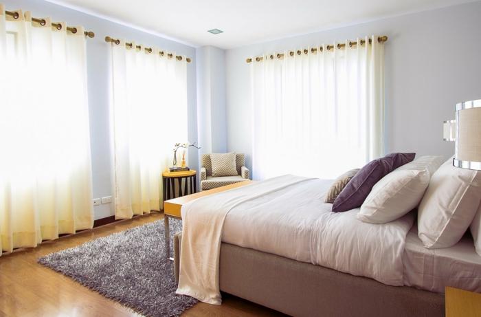 Schlafzimmer Teppich, großes Bett, weiße Gardinen, lila Kissen, flauschige Teppiche Inspiration