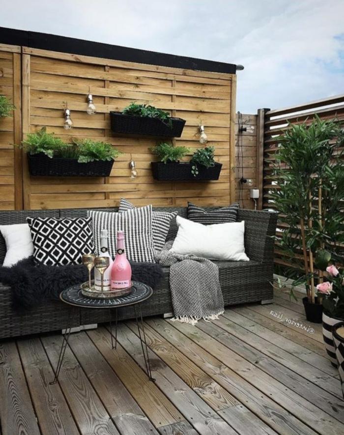 Garten Trennwand Holz mit großen Pflanzer, Sichtschutz Ideen für die Terrasse, großer schwarzer Sofa mit kleinen Kissen, kleiner runder Tisch