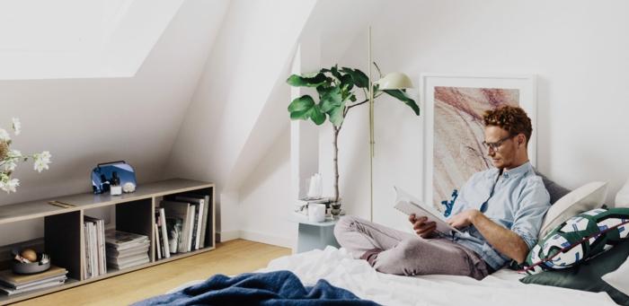 Mann liest eine Buch im Bett, kleine offene Kommode, große grüne Pflanze Tylko Möbel