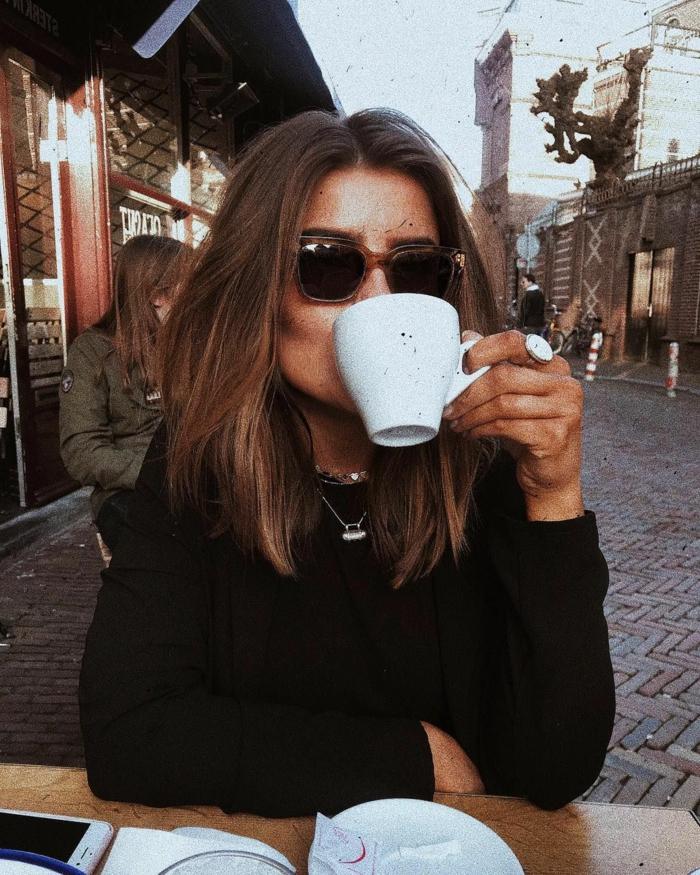 Frau trink Kaffee in einem Cafe, Vsco Girl, schwarze Bluse, Kurzhaarfrisuren Bob Trend, schwarze Sonnenbrillen