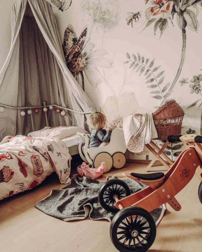 kleines Kind spielt in seinem Zimmer, viele Spielzeuge, Wandgestaltung Tapete mit floralen Motiven, Deko Ideen Wand
