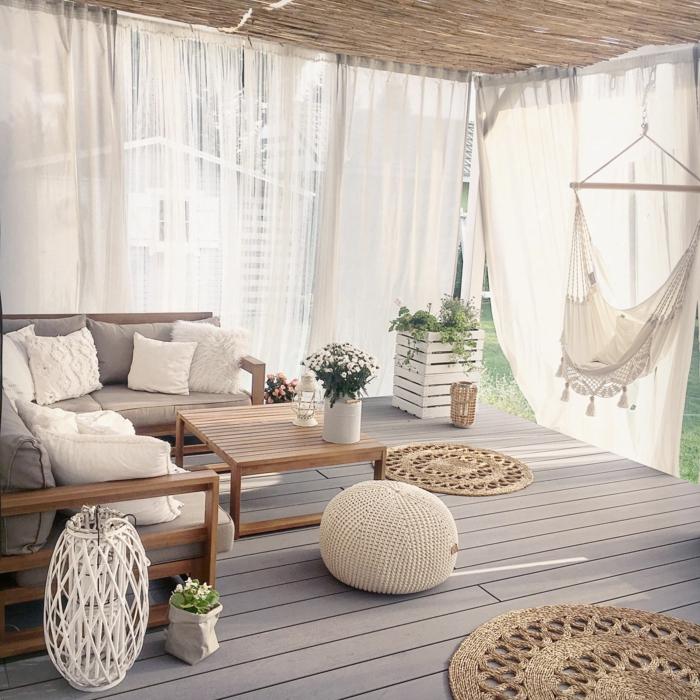 Terrassengestaltung mit Sichtschutz aus weißen Gardinen, großes Ecksoda mit grauen Kissen und Polsterung, Dekoration mit Hängematte