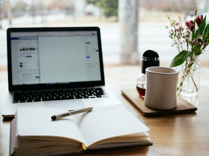 Laptop und ein aufgeschlagenes Buch auf einem Tisch, weiße Tasse, Berufsbegleitende Weiterbildung., sgd Deutschland