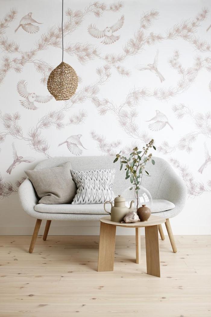 Außergewöhnliche Wandgestaltung Wohnzimmer, kleines Sofa in grau, runder Tisch aus Holz, Wandgestaltung Ideen, Tapet mit Vögel und floralen Motiven