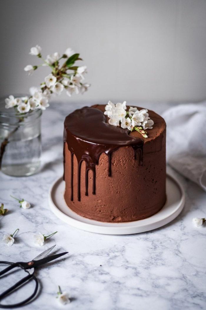 drip cake rezept mit schokolade, schokoladenkuchen dekoriert mit ganache und kleinen weißen blüten