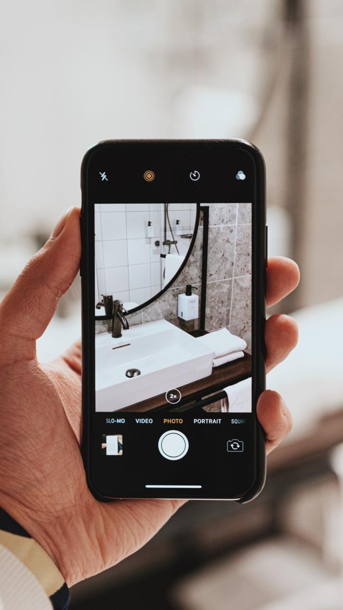 Hand hält ein schwarzes Handy mit einem Foto vom runden Badspiegel, runder Spiegel für Badezimmer Inspiration