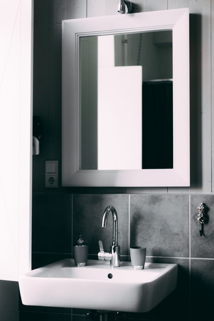Spiegel mit weißem Rahmen, große graue Fliesen, Badezimmerspiegel beleuchtet, graue Tasse für Zahnbürsten,