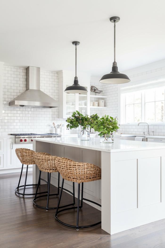 Bar Korbstühle, Hängelampen in schwarz, monochrom weiße Küche, Vasen mit grünen Blumen, Kücheninsel mit Tisch