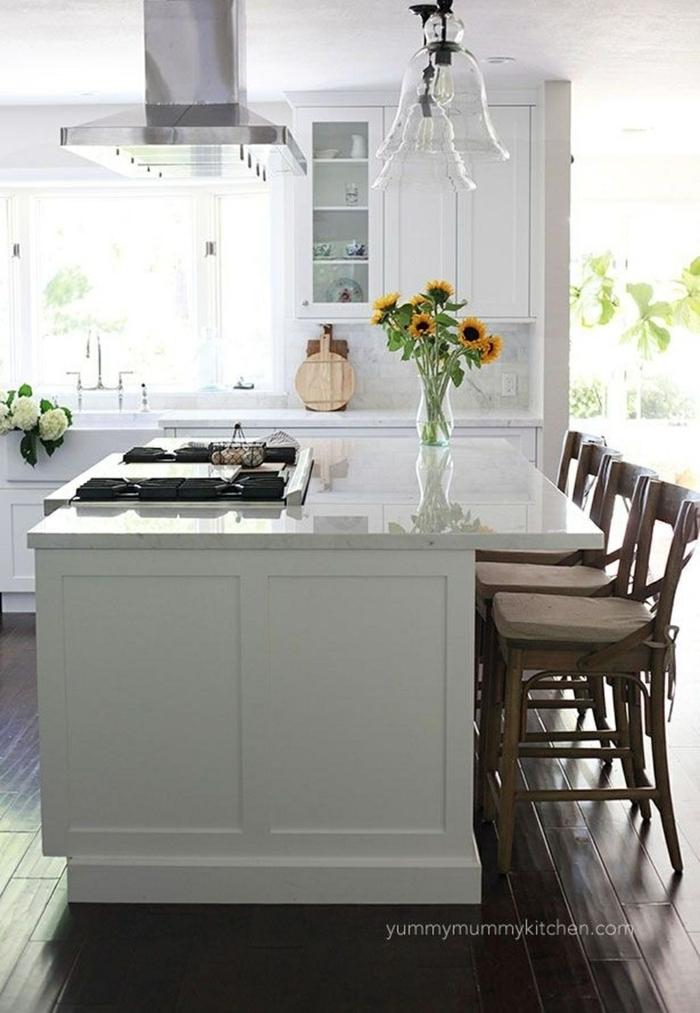 Moderne Küche mit Insel und Sitzgelegenheit, Vase mit Sonnenblumen, weiße Küchenschränke, Minimalistisches Design