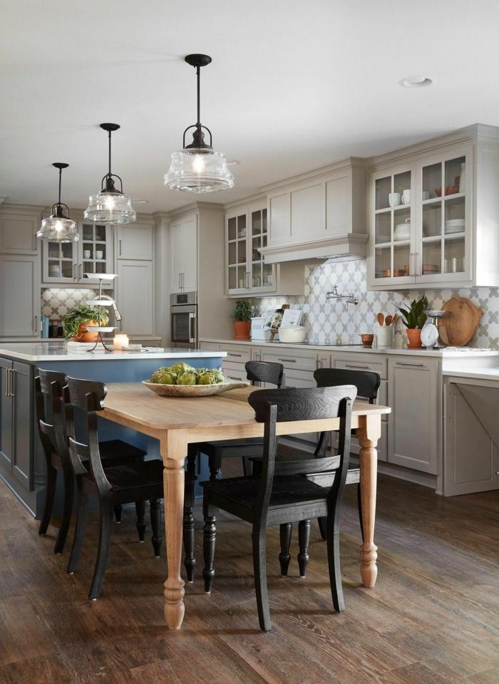 blaue Kücheninsel mit Sitzgelegenheit, Tisch aus Holz, helle Küchenschränke, fünf schwarze Stühle, Innengestaltung Ideen