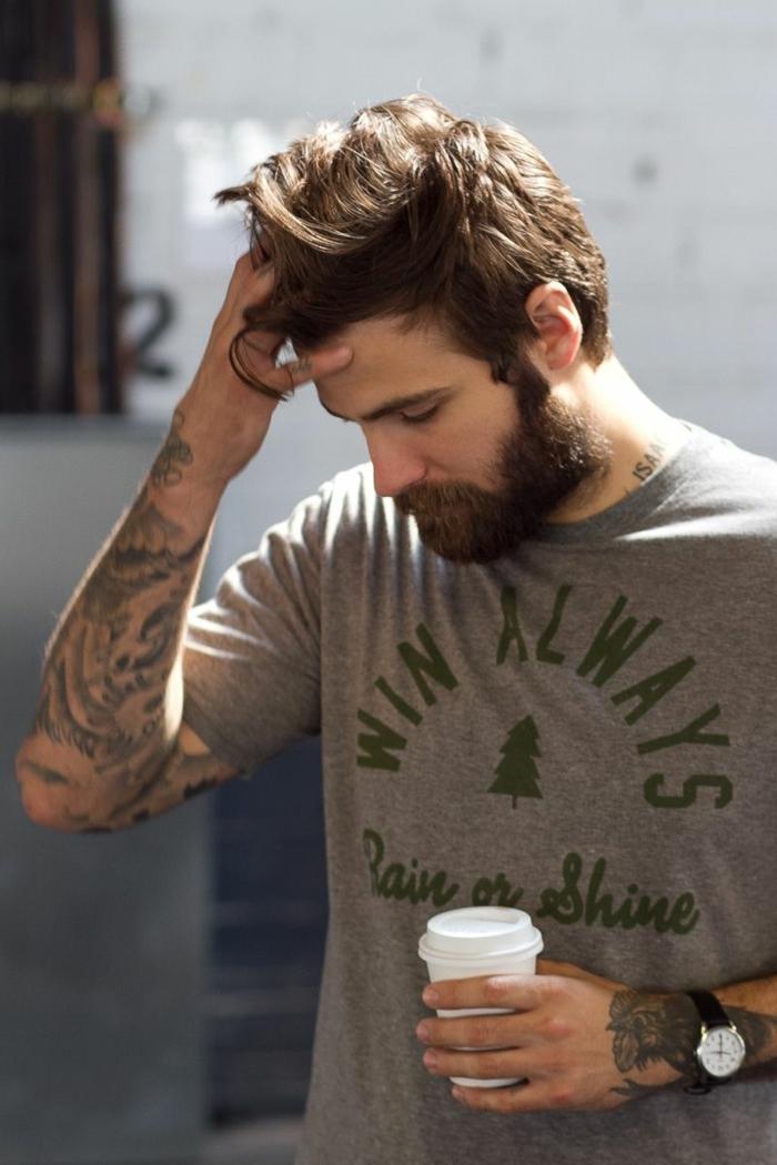 Männer Frisuren Kurz 2020 Trend, Mann mit vielen Tattoos auf dem Arm, hält eine weiße Tasse Kaffee, angezogen im grauen T-Shirt