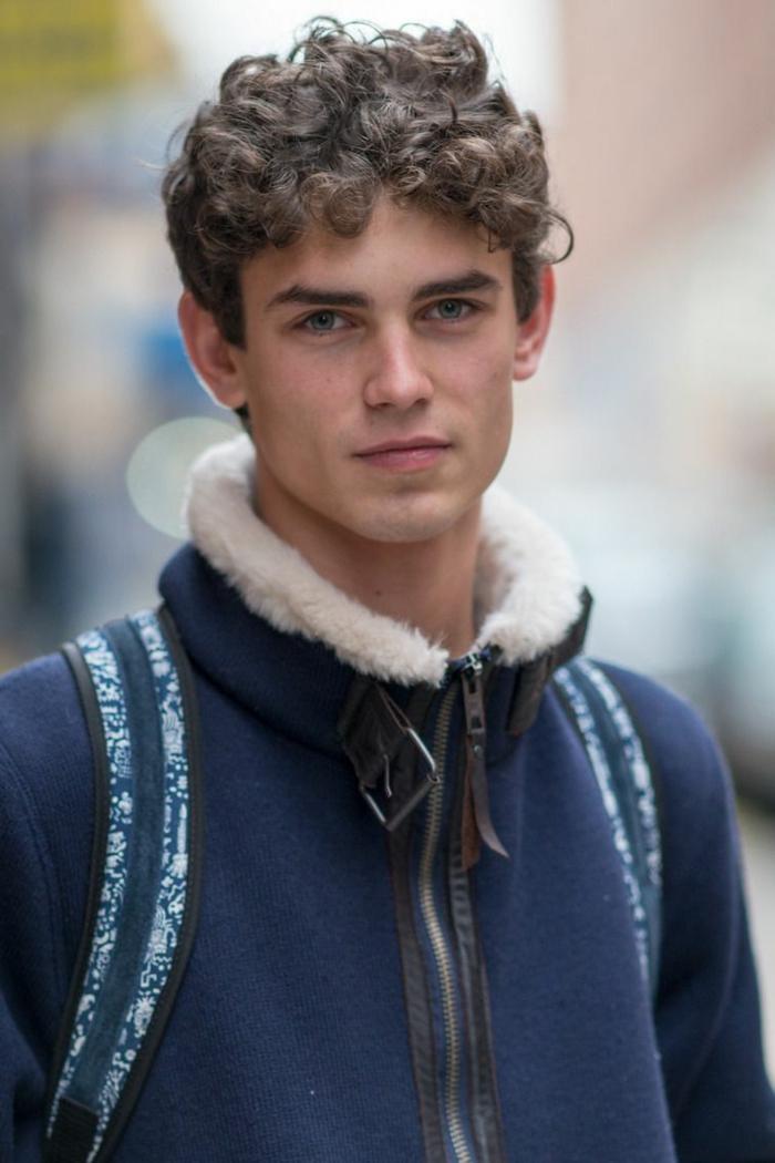 Männer Kurzhaarschnitt, junger Mann mit braunen und lockigen Haaren, blaue Jacke mit weißem Kragen, street style inspiration