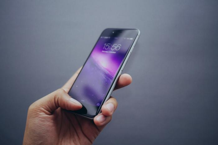 eine hand mit einem grauen smartphone mit einem bildschirm mit schutzfolie, das handy optimal schützen