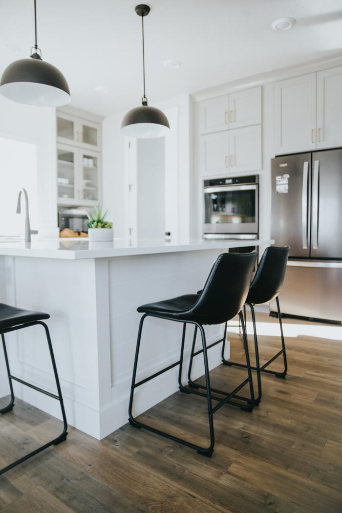 Kücheninsel klein, zwei hängende schwarze Lampen aus Metall, weiße Küche mit Bodenbeleg aus Holz, Küche moderne Inneneinrichtung