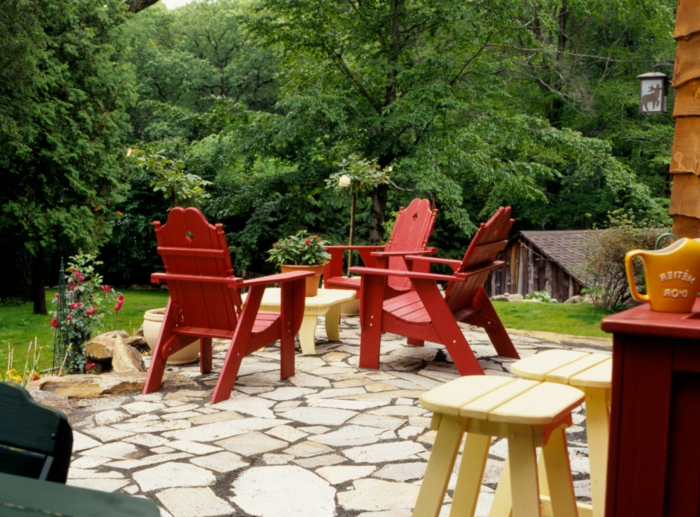drei rote gartenstühle ideen gartengestaltung mit steinen außeneinrichtung grüne bäume