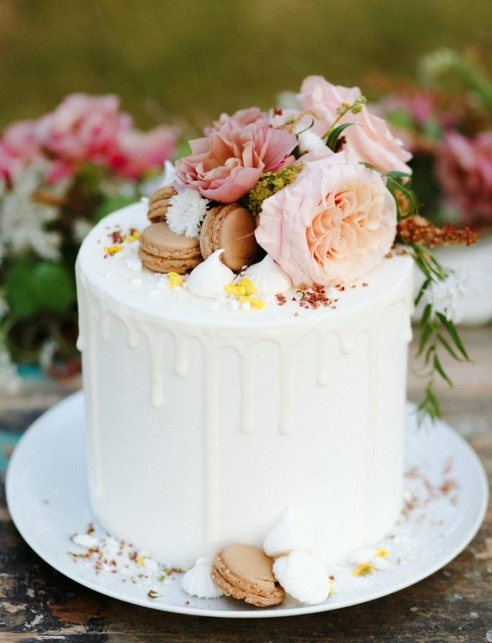 drip cake geburtstag, leckere torte mit weißer schokolade dekroiert mit maccarons und blüten