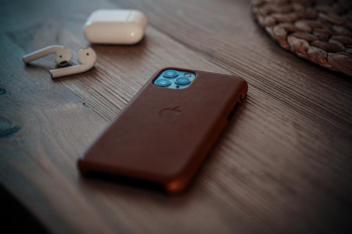 zuwei weise kopfhörer, ein tisch aus holz und ein smartphone mit einer braunen handyhülle, das handy richtig schützen