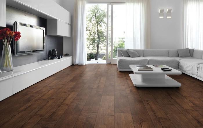 ein wohnzimmer mit bodenbelag laminat graues sofas ein weißer tisch blumentopf mit roten blumen