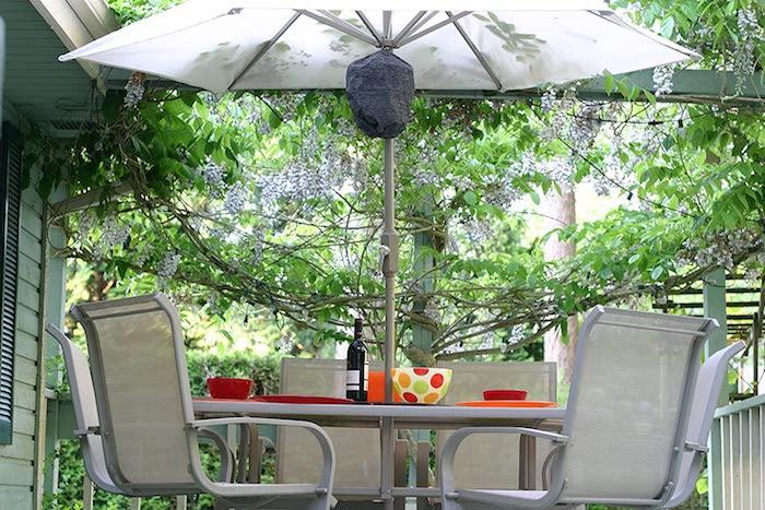 eine gekaufte graue wespennest attrappe waspinator ein sonnenschirm zuwei stühle im garten und ein tisch wie kann man wespen vertreiben