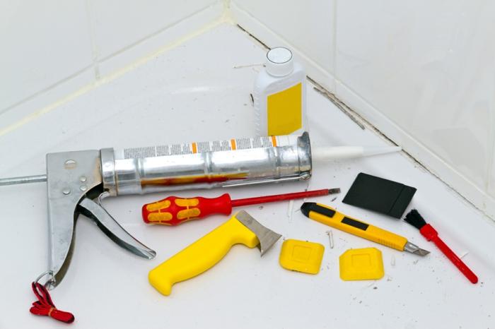 badewanne mit weißen fliesen, eine pistole mit silikon für die fugenm ein gelber cuttermesser, eine diy anleitung wie man das alte silikon entfernen kann